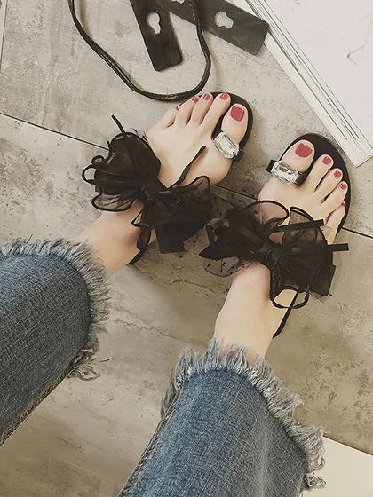 Arco negro y cristal adornado de sandalias planas